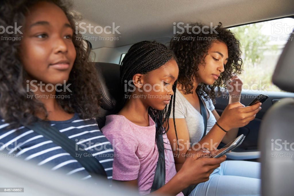 Teenage Children Using Digital Devices On Family Road Trip stock photo