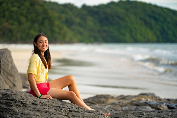 Teenage chinese girl poses against ocean background stock photo