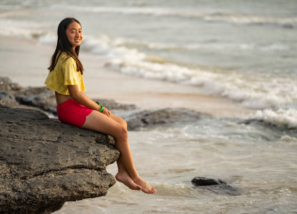 Teenage chinese girl sitting at the edge of a rock outcrop stock photo