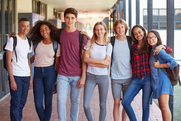 Teenage classmates standing in high school hallway stock photo