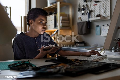 istock Teenage computer genius busy at work 1146553016