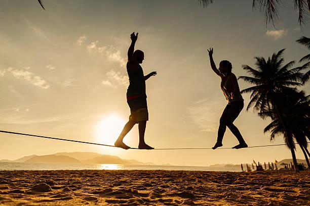 teenager paar ausgleichende slackline am strand - slackline stock-fotos und bilder