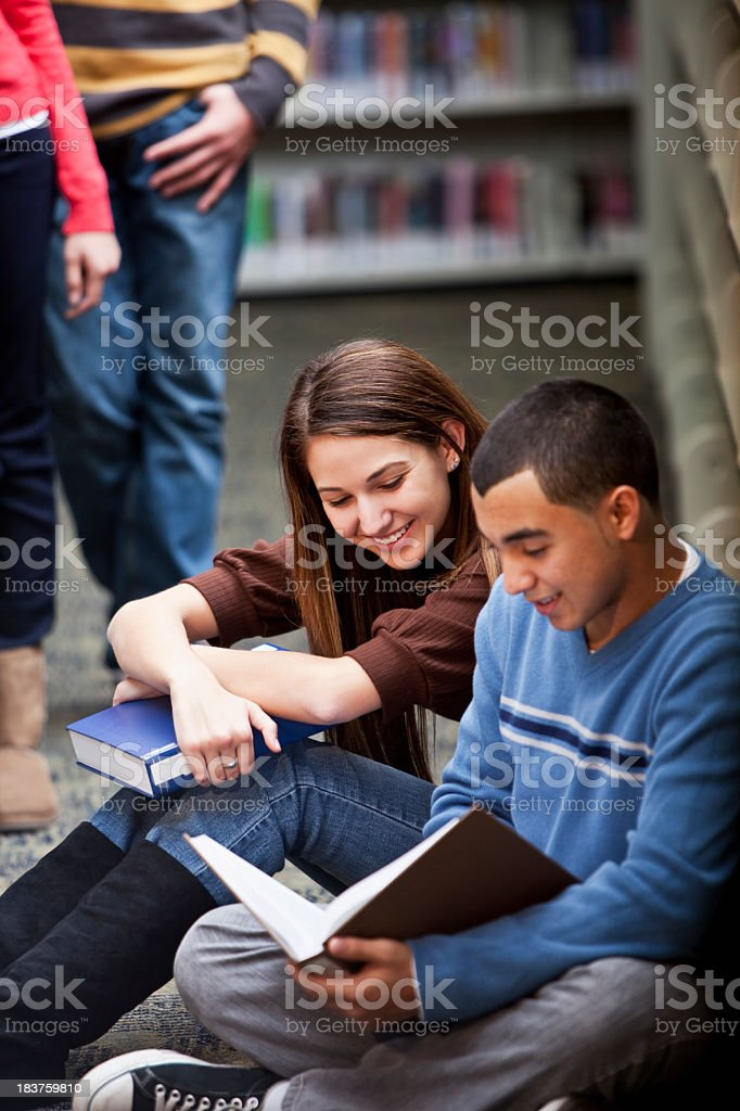 Teenage couple hanging out in library royalty-free stock photo