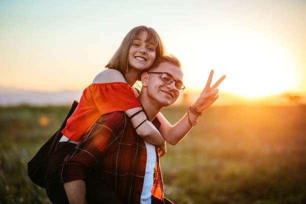 Teenage couple having hun Cute teenage couple having piggyback fun in nature at sunset. cute teen couple stock pictures, royalty-free photos & images