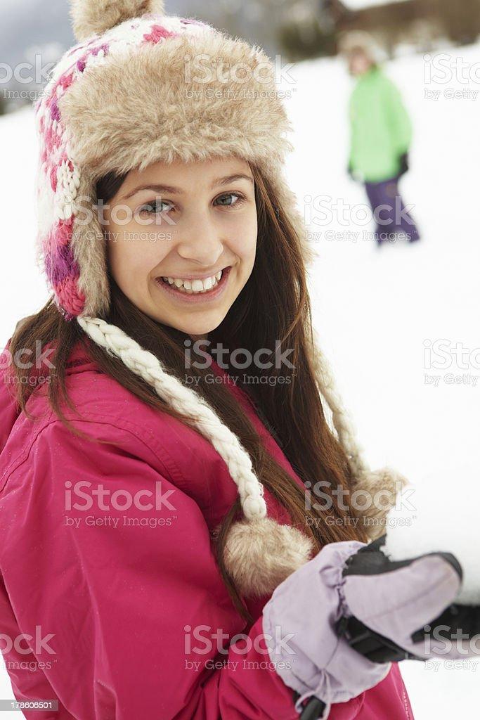 Teenage Couple Having Snowball Fight Wearing Fur Hats stock photo