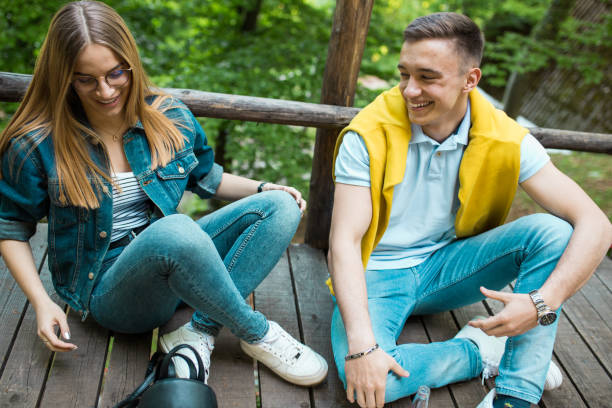 Teenage couple is taking a break from walking in forest stock photo