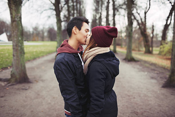 Teenage couple kissing outdoor in the park Loving young couple kissing outdoors in the park. Mixed race man and woman. Teenage love. cute teen couple stock pictures, royalty-free photos & images