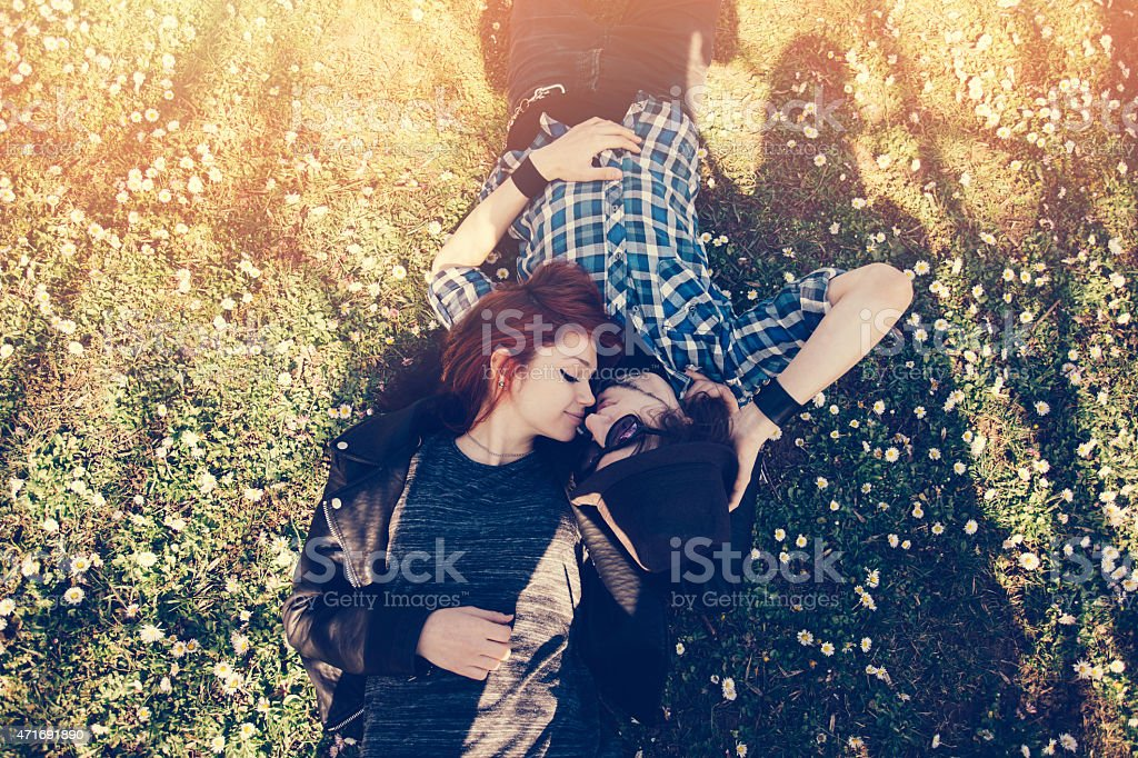 Teenage couple lying down at the grass stock photo