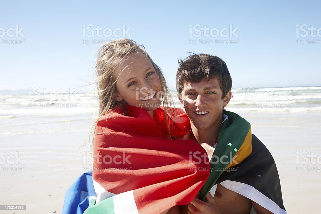 Teenage couple on the beach wrapped in South African flag royalty-free stock photo