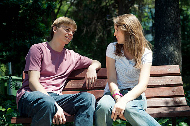 Teenage couple on the bench Teenage couple sitting on the bench in the park cute teen couple stock pictures, royalty-free photos & images