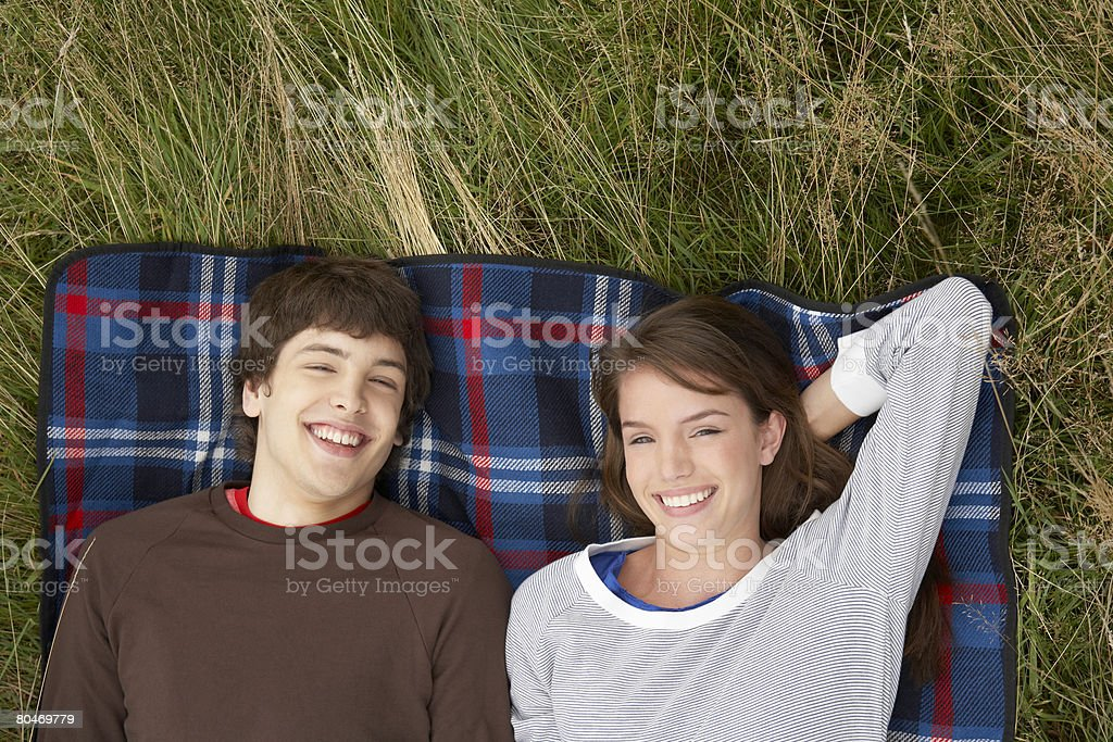 Teenage couple relaxing in a field 免版稅 stock photo