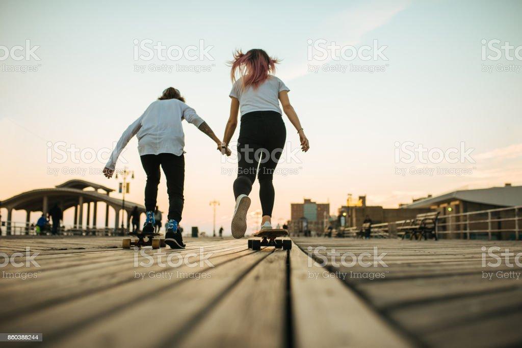Teenage couple riding longboards stock photo