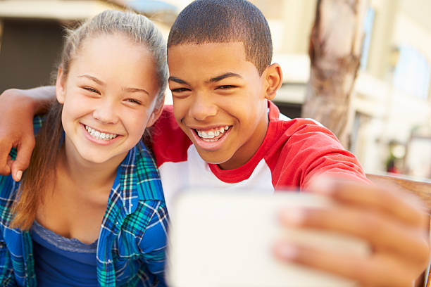 Teenage Couple Sitting On Bench In Mall Taking Selfie stock photo