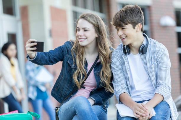 teenage couple take selfie together during school break - compagni scuola foto e immagini stock