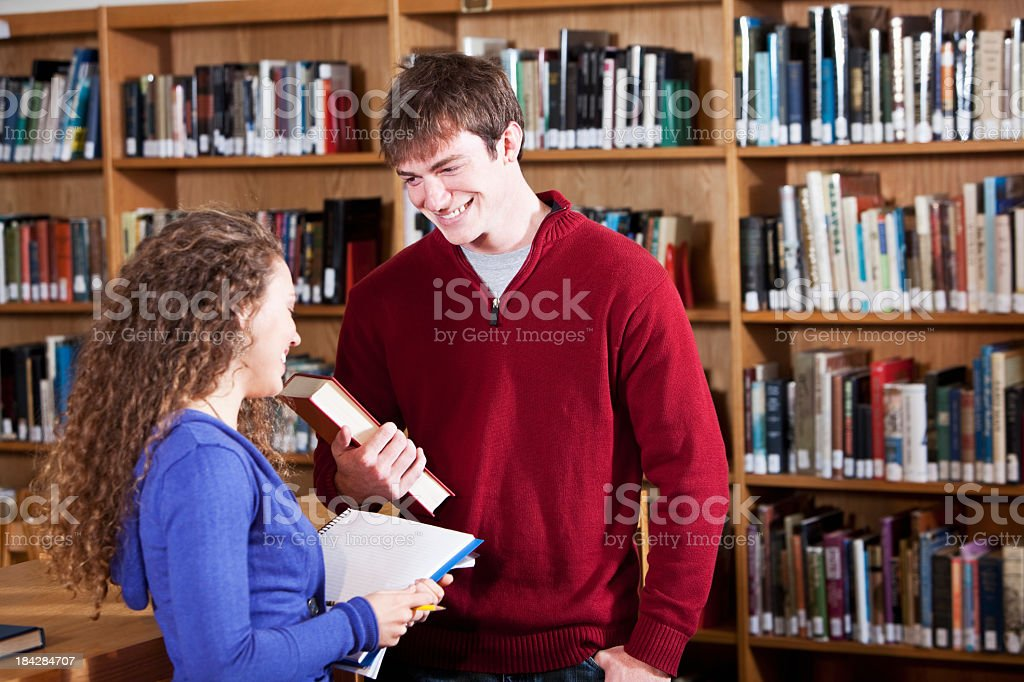 Teenage couple talking in library royalty-free stock photo