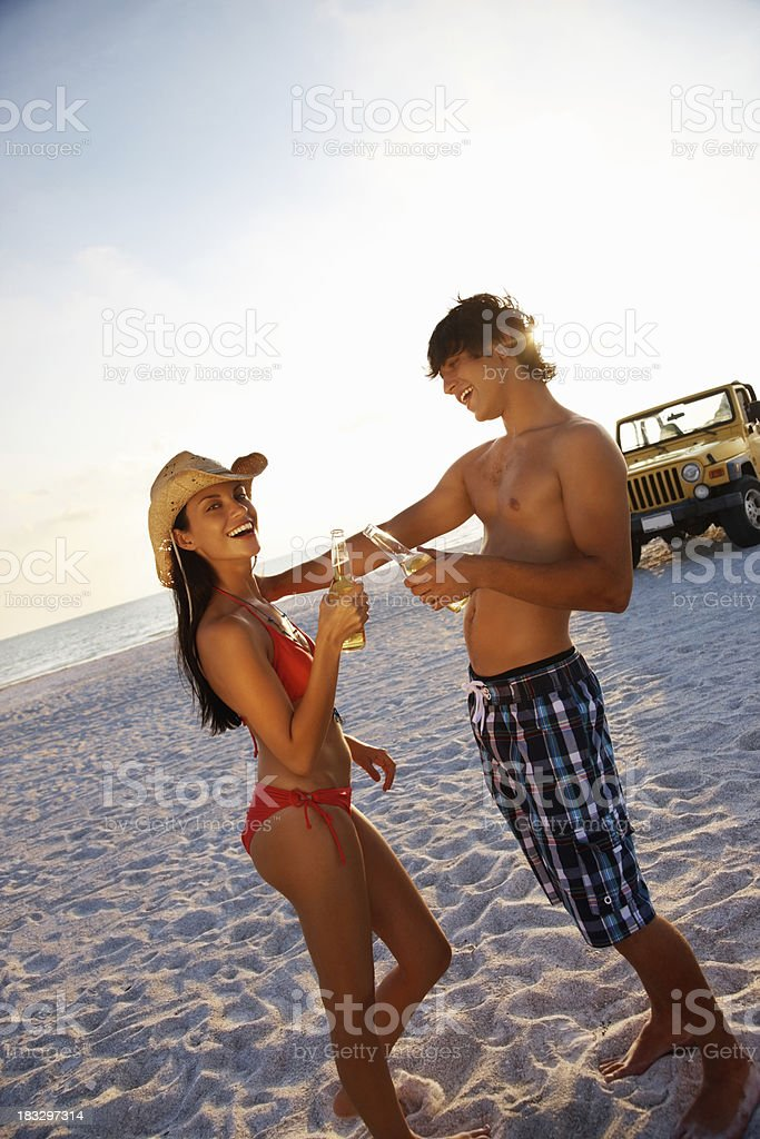 Teenage couple toasting beer with jeep in background on beach royalty-free stock photo