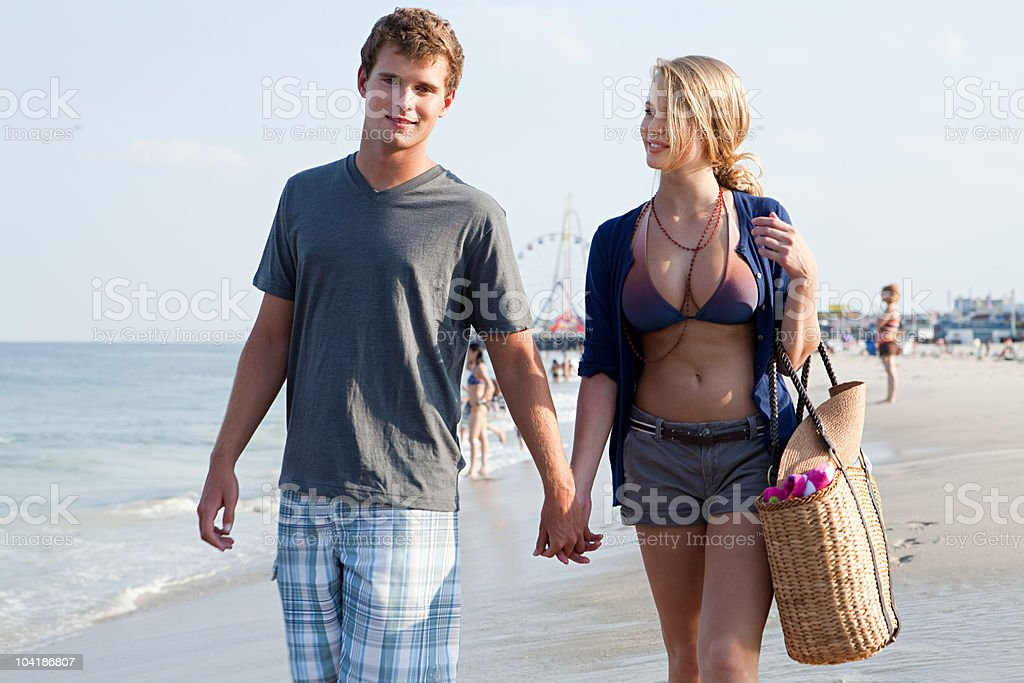 Teenage couple walking hand in hand on beach stock photo