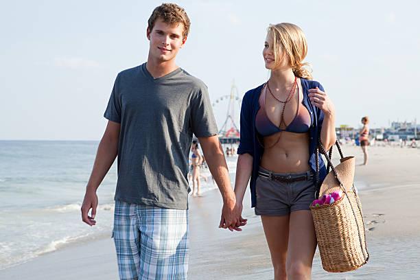 jeune couple marchant main dans la main sur la plage - fille 16 ans photos et images de collection
