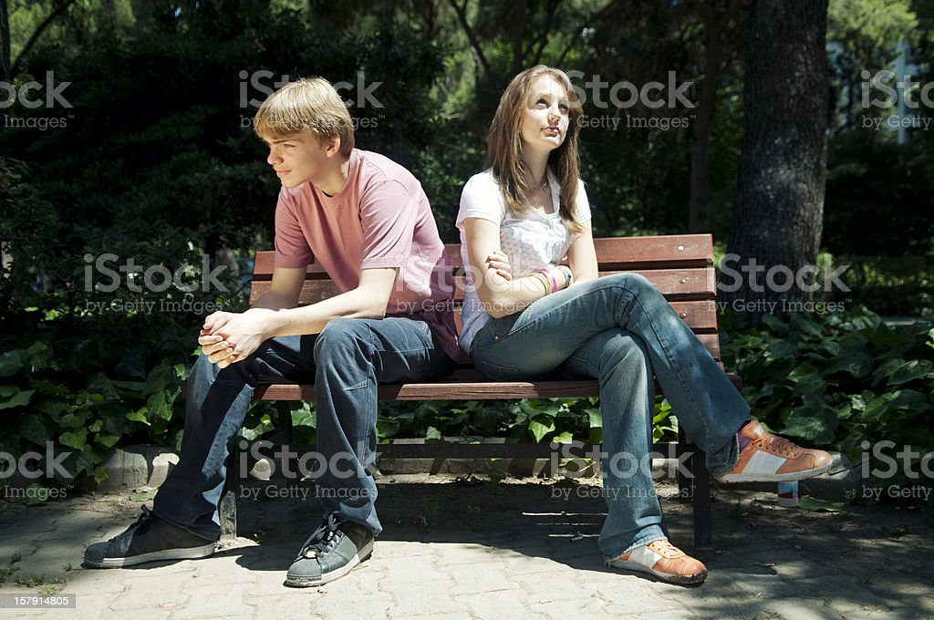 A teenage couple with their backs to each other stock photo