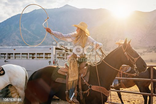 Young blonde teenage cowgirl sitting on her horse training tricks with her lasso at the rodeo arena. Real People Portrait. Utah, USA.