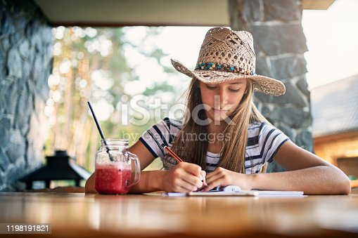 Teenage girl is sitting by the wooden table on terrace of a small wooden cabin. The girl is doing homework.