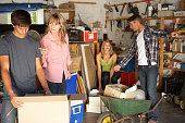 Teenage Family Clearing Garage For Yard Sale With Parents Telling Off Children