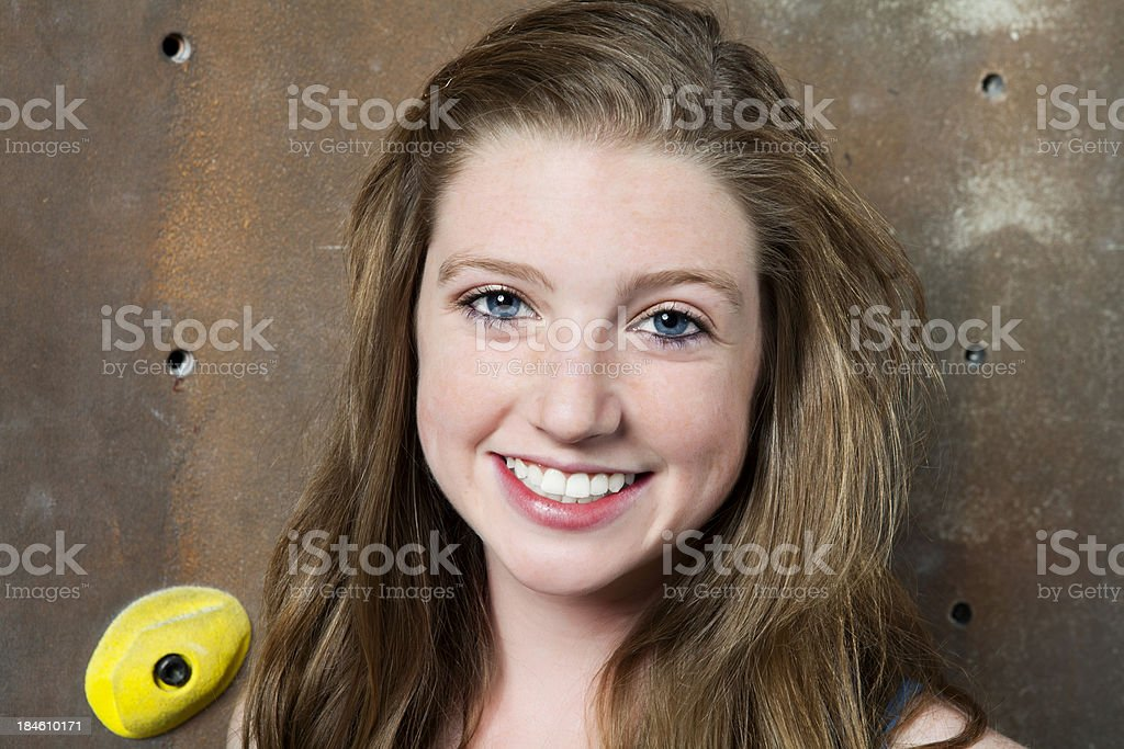 Teenage female leaning against climbing wall royalty-free stock photo