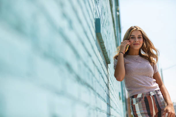 Teenage Female Standing in Front of Blue Brick Wall Using Smart Phone Urban Photo Series In Western Colorado Teenage Female Standing in Front of Blue Brick Wall Using Smart Phone Technology Urban Photo Series Urban (Shot with Canon 5DS 50.6mp photos professionally retouched - Lightroom / Photoshop - original size 5792 x 8688 downsampled as needed for clarity and select focus used for dramatic effect) eyecrave stock pictures, royalty-free photos & images