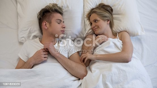 504371332 istock photo Teenage female waking up and tenderly looking at her sleeping boyfriend, love 1061833020