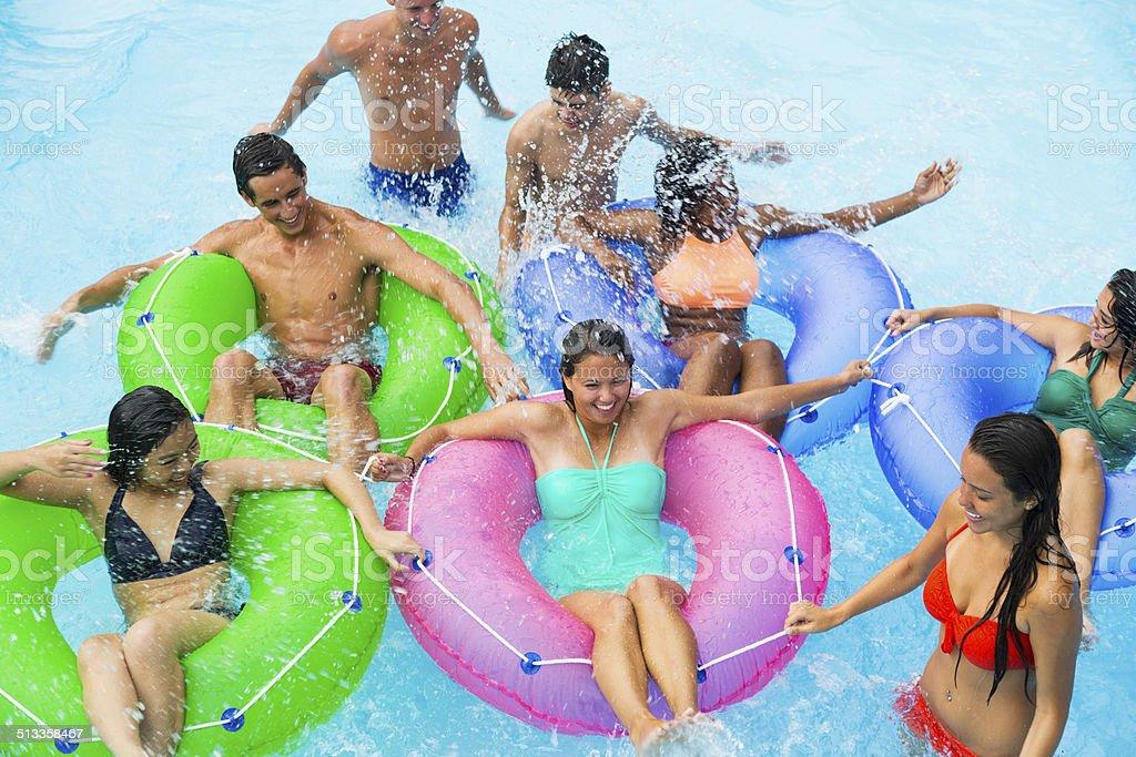 Teenage friends floating on innertubes stock photo