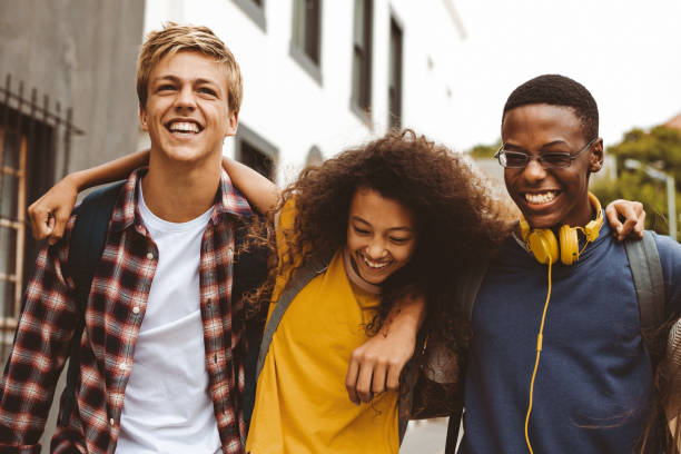 Teenage friends having fun outdoors Close up of three college friends standing in the street with arms around each other. Cheerful boys and a girl wearing college bags having fun walking outdoors. jacoblund stock pictures, royalty-free photos & images