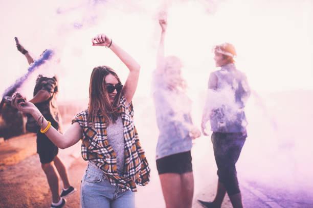 teenager freunden spaß mit rauchbomben in den stadtstraßen - lila waffe stock-fotos und bilder