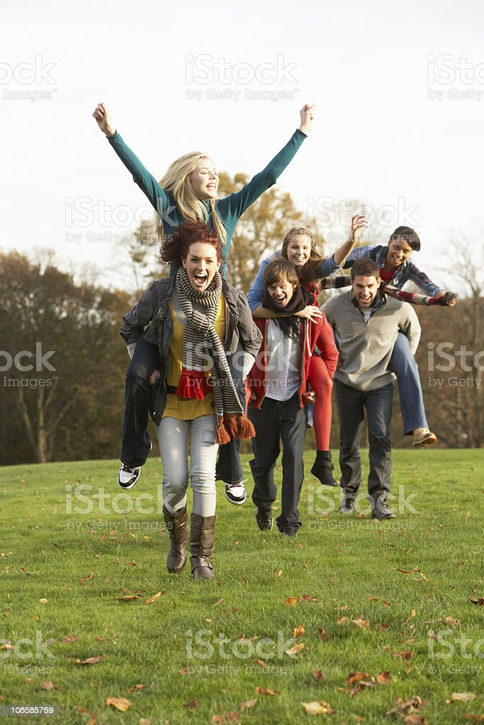 Teenage Friends Having Piggyback Rides In Autumn Landscape royalty-free stock photo