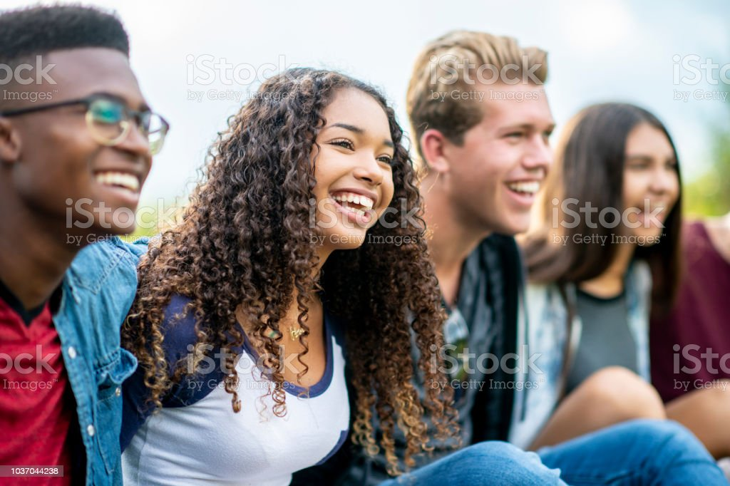 Teenage friends laughing outside stock photo