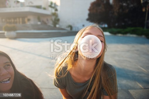 Two teenage girls having fun in the urban part of the city. They are making bubbles with bubble gum.
