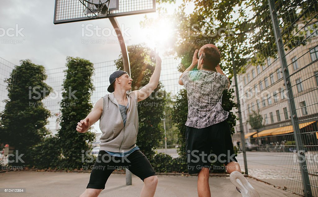 Teenage friends playing a game of basketball stock photo