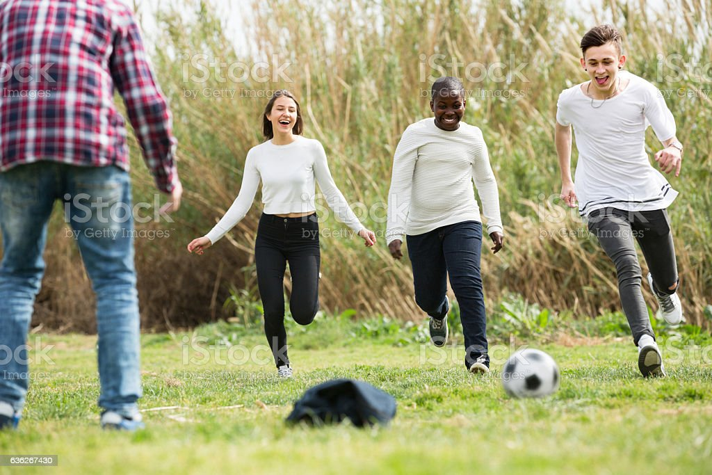 teenage friends playing football stock photo