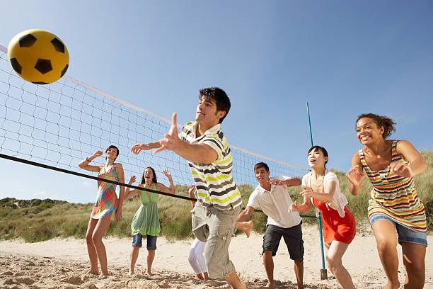 Teenage friends playing volleyball on beach stock photo