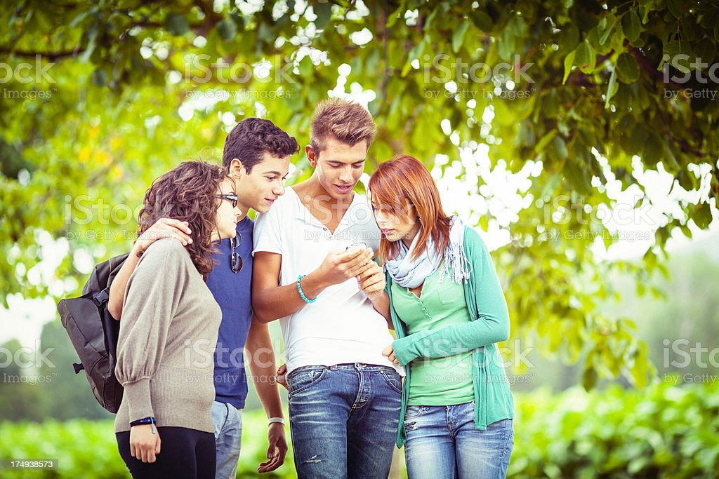 Teenage friends reading text message royalty-free stock photo