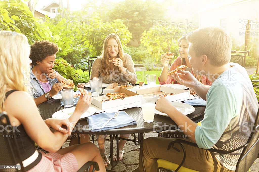 Teenage friends sharing pizza box take-out lunch outdoors at backyard...