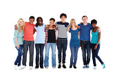Multi-ethnic group of teenagers stand in a row with arms around one another. Horizontal shot.