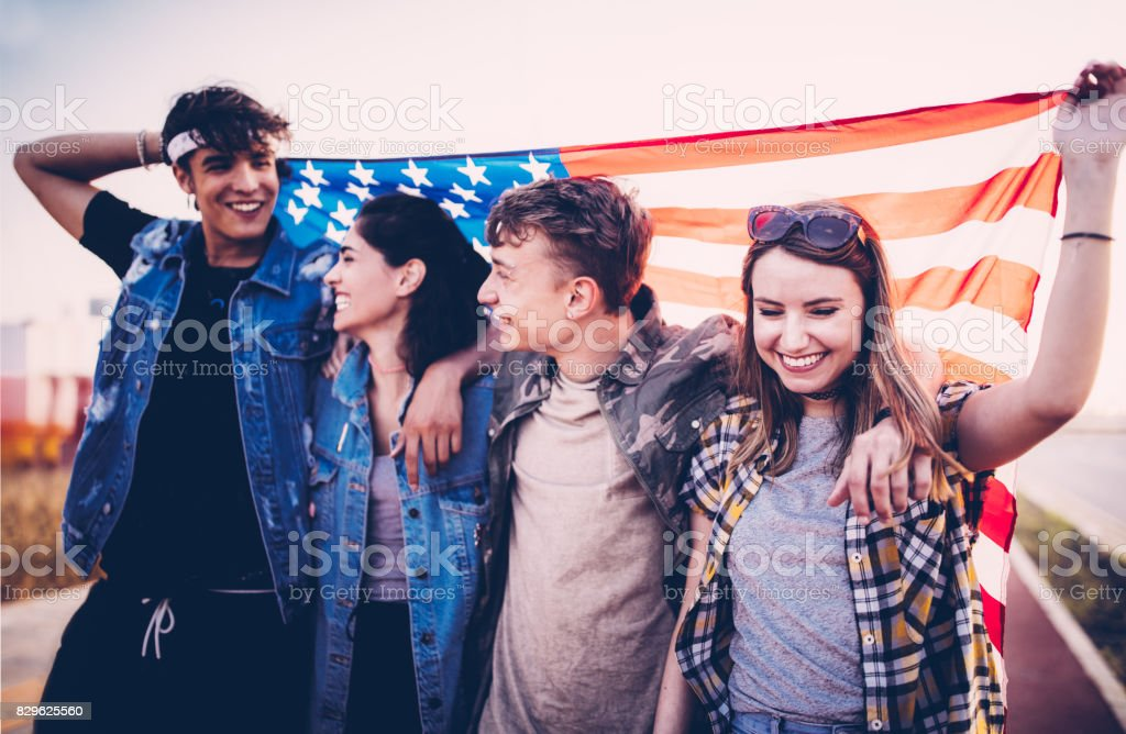 Teenage friends walking in the streets with an American flag stock photo