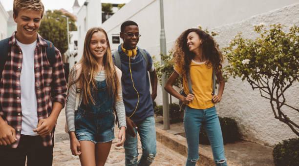 Teenage friends walking on street stock photo