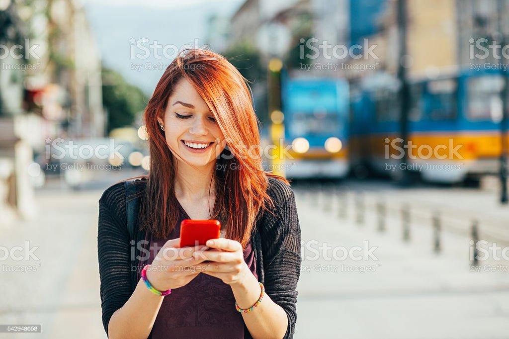 Adolescente gilr avec smartphone en plein air à la lumière du soleil - Photo