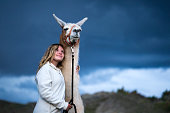 Portrait of a blond teenage girl with a white and brown Carra llama animal in the San Juan Mountains on a cloudy stormy day, Silverton, Colorado, USA