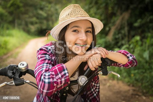 Close-up lifestyle outdoor portrait of a teenage girl and a bicycle