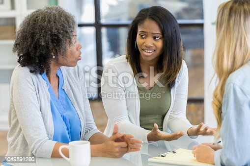 Upset teenage girl gestures while arguing with her mom during a counseling session.