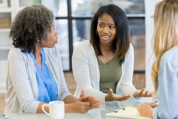 Teenage girl and her mom talk during counseling session Upset teenage girl gestures while arguing with her mom during a counseling session. age contrast stock pictures, royalty-free photos & images