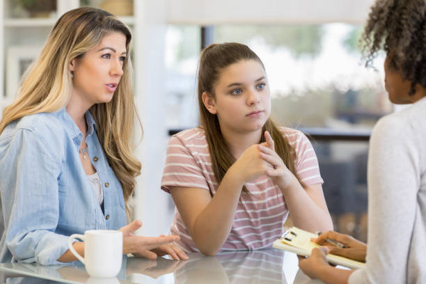 teenage girl and her mom talk with school counselor - school counselor stock pictures, royalty-free photos & images