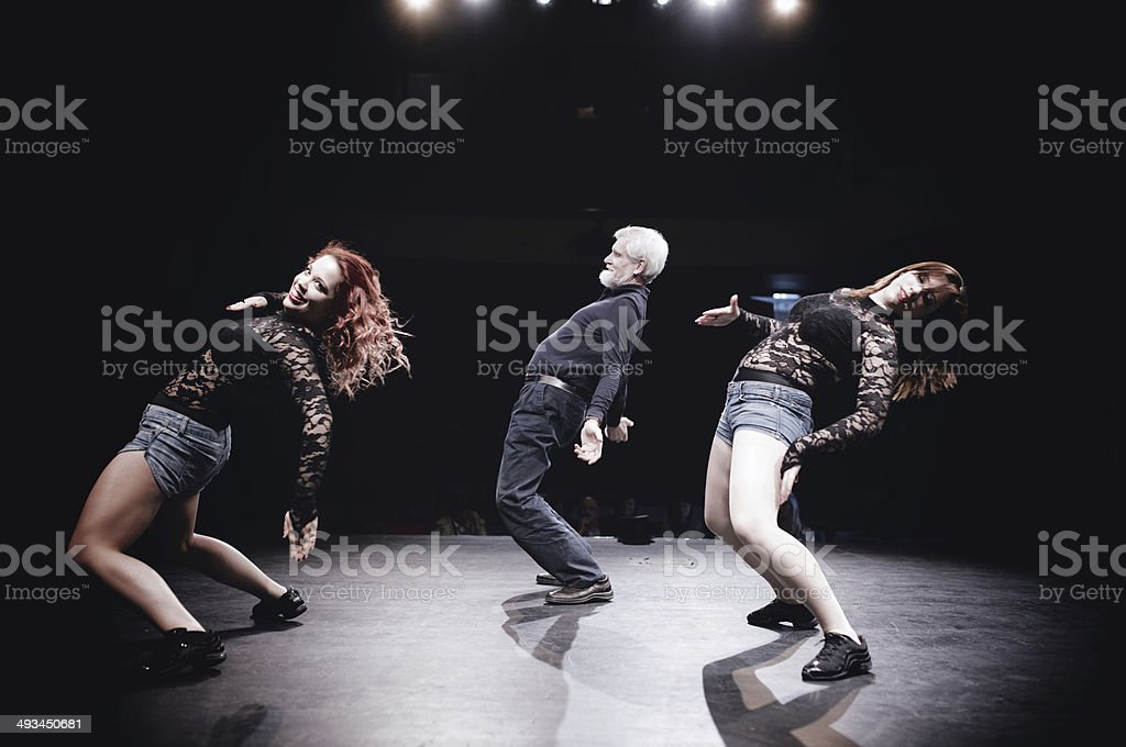 Teenage girl and senior man doing dance routine on stage